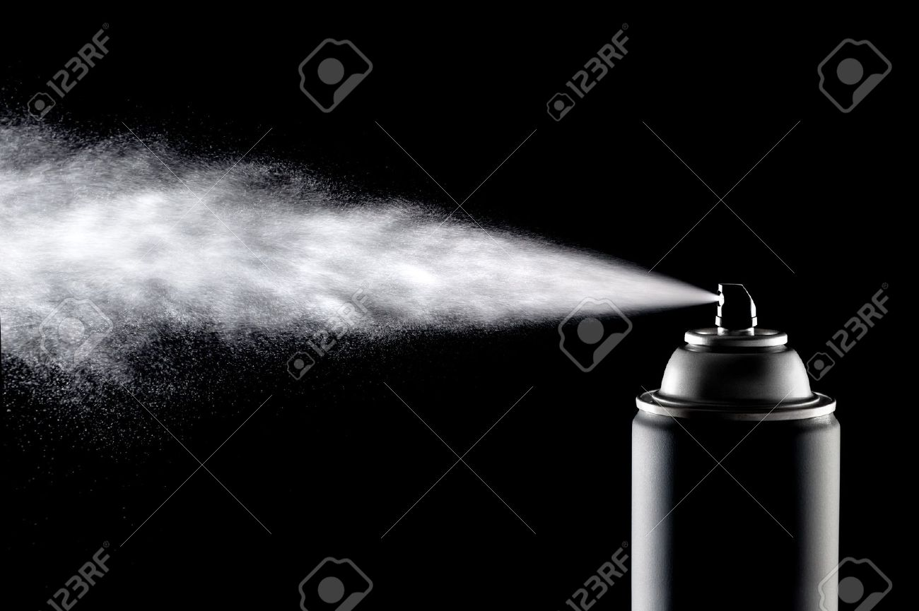 An aerosol can of spray dispensing its content against a backlit black background. Stock Photo
